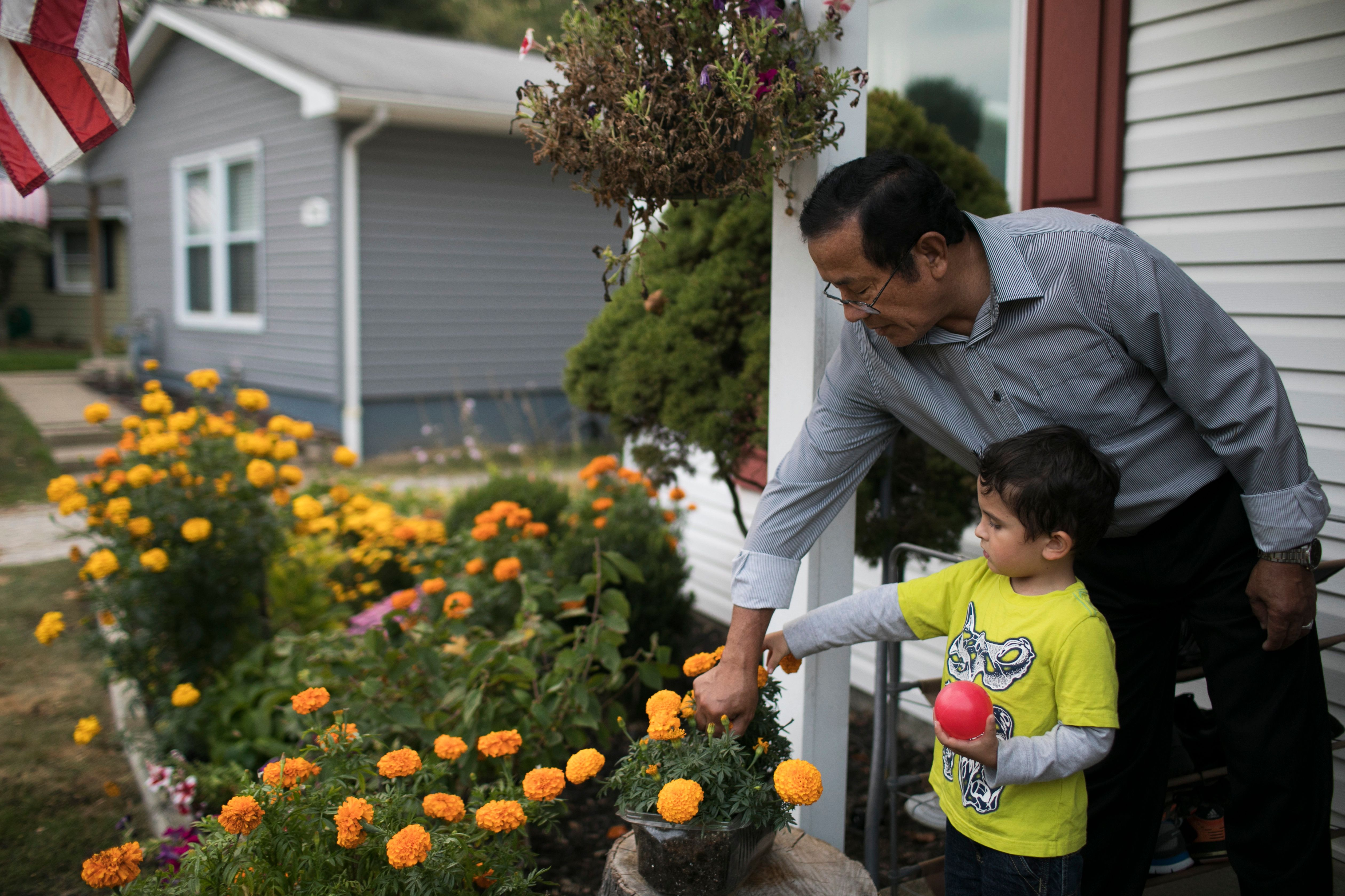Dhan Tumbapoo and his grandson Silas water their marigolds at home at in Cuyahoga Falls, OH on September 27, 2017.