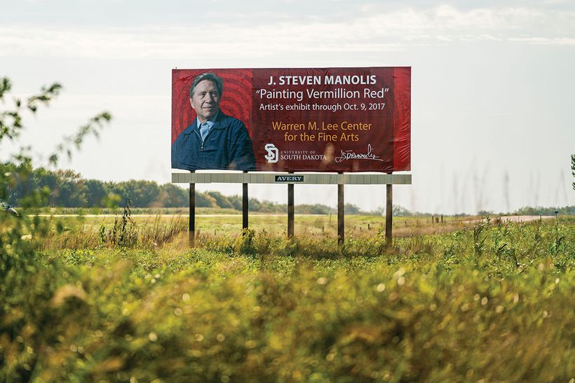 "Billboard commemorating J. Steven Manolis' ""Painting Vermillion Red"" exhibition. Highway 50, South Dakota."