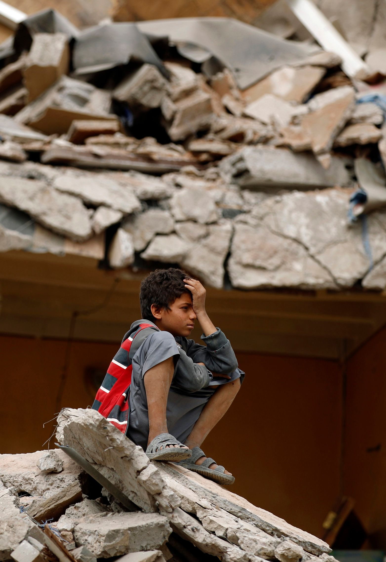 A Yemeni boy reacts as he sits on the debris of a house hit in an air strike in the residential southern Faj Attan district of the capital, Sanaa, on August 25, 2017. The attack destroyed two buildings in the southern district, leaving people buried under debris, witnesses and medics said. / AFP PHOTO / MOHAMMED HUWAIS        (Photo credit should read MOHAMMED HUWAIS/AFP/Getty Images)