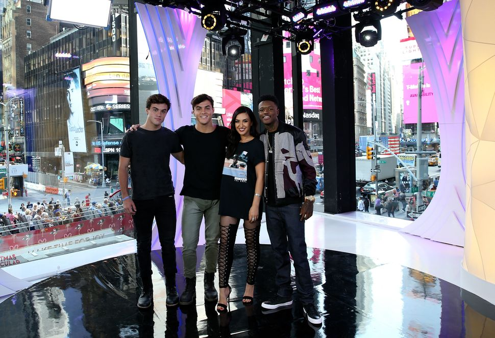 """TRL"" squad members Ethan Dolan, Grayson Dolan and Tamara Dhia with ""TRL"" host DC Young Fly in front of the MTV studio's icon"