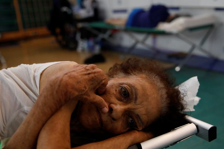 Hilda Colon wakes up after sleeping in a shelter set up at the Pedrin Zorrilla coliseum, after Hurricane Maria destroyed the