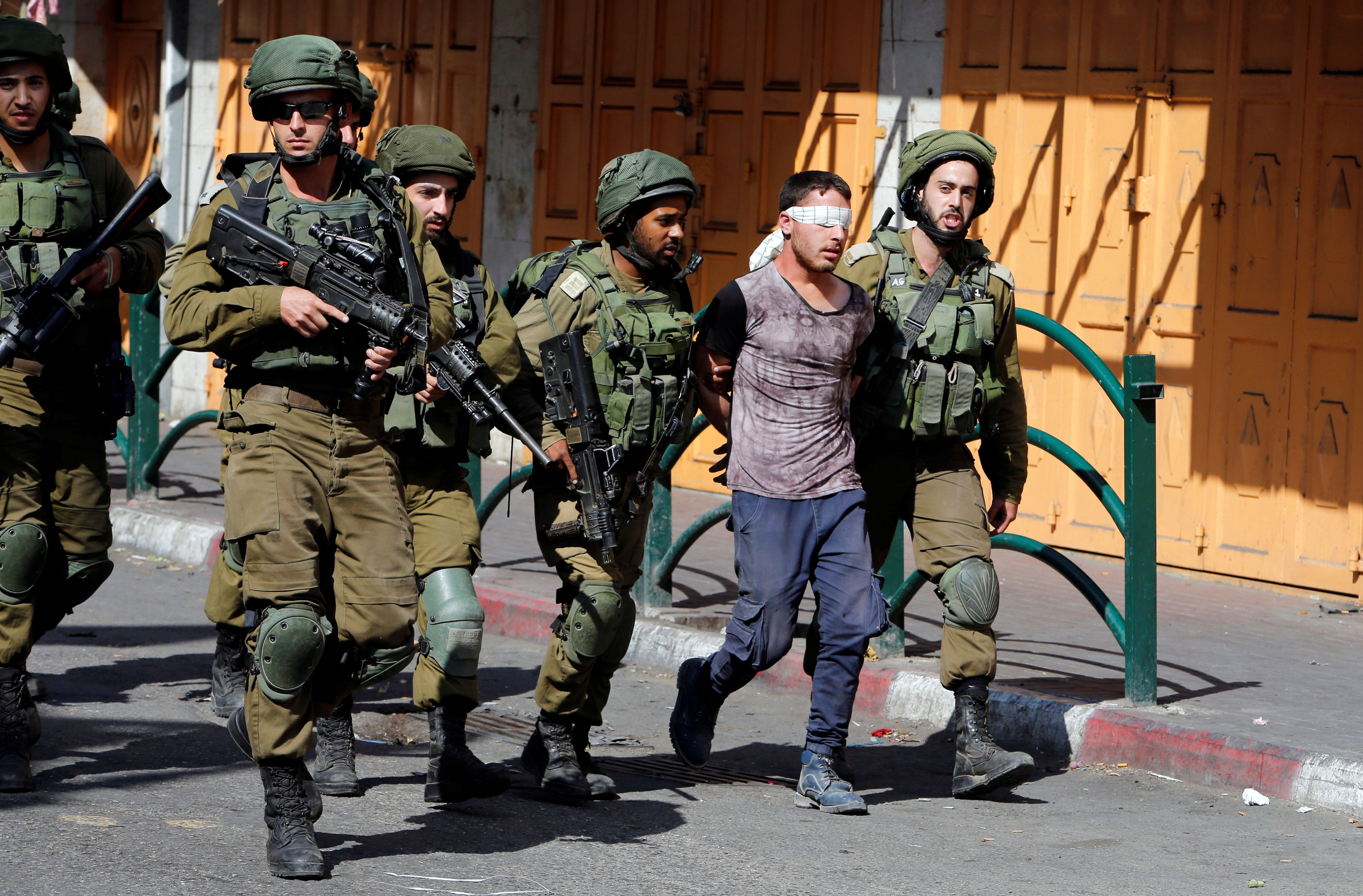 Israeli soldiers detain a Palestinian protester during clashes in the West Bank city of Hebron, September 29, 2017. REUTERS/Mussa Qawasma