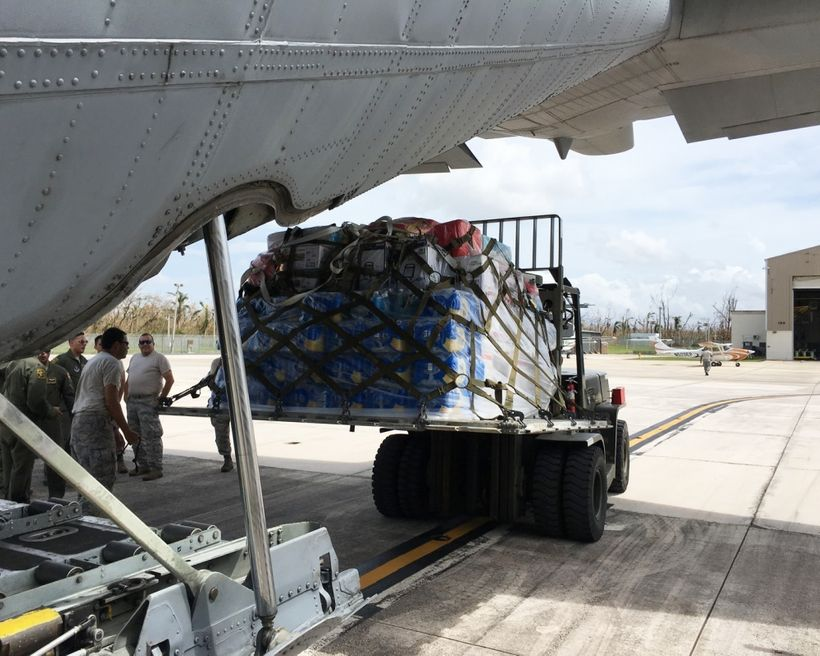 Airmen from the Puerto Rico Air National Guard unload supplies from a C-130 Hercules at Muniz Air National Guard Base in Puer