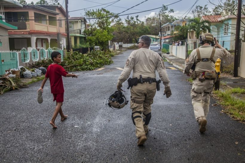A young boy walks with Air and Marine Operations agents as they walk through a neighborhood checking on residents outside of