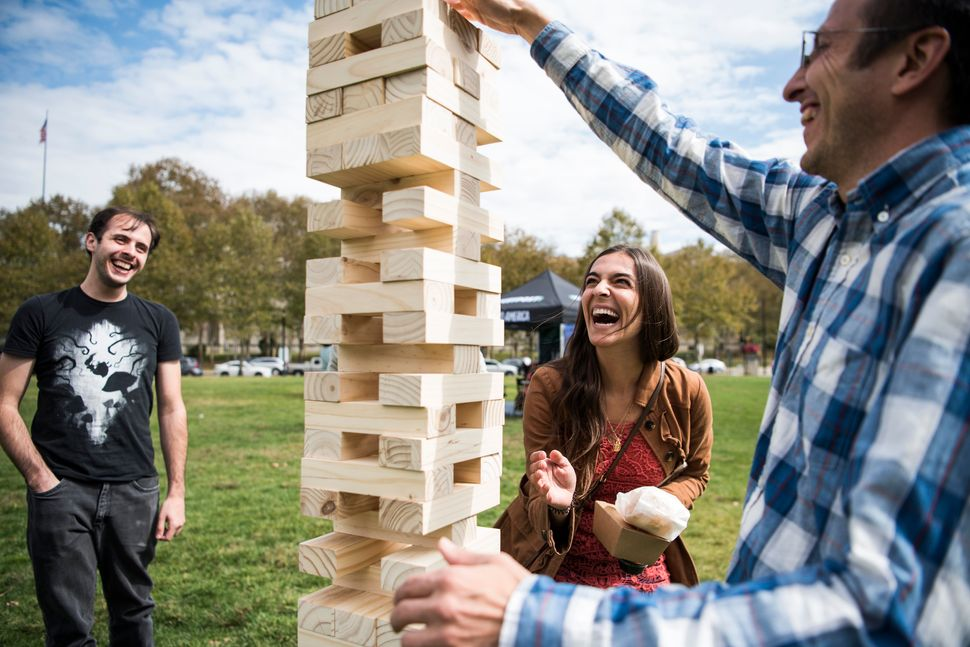 Sara Longo and Iliah Nourbakhsh play a game of jumbo Jenga while others watch.