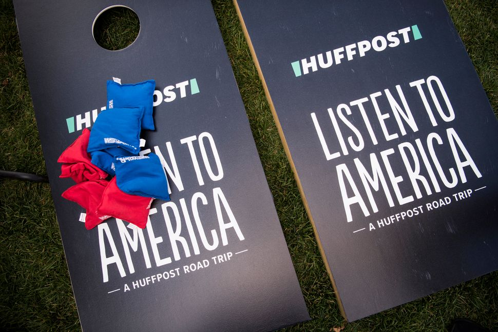 A game of cornhole sits at the HuffPost activation site.