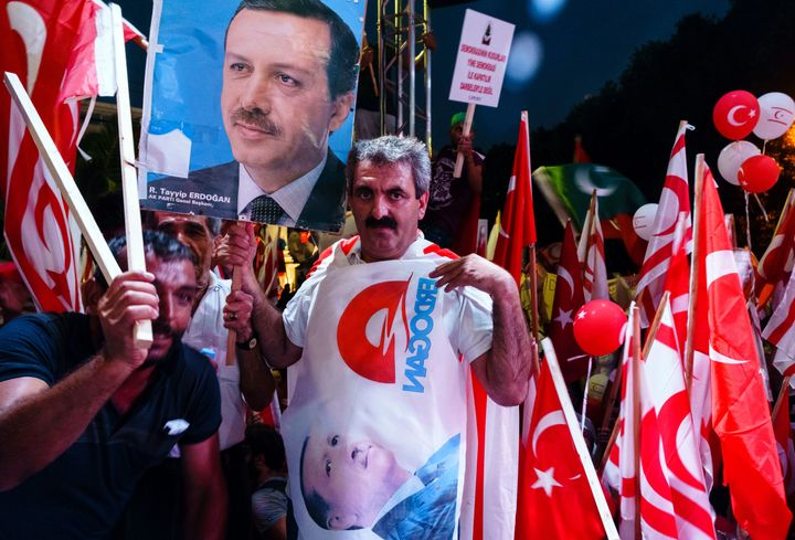 Turkish Cypriot demonstrators wave Turkish and Turkish Cypriot flags during a mass rally in support of Turkey's Erdogan following a failed coup that aimed to oust him.
