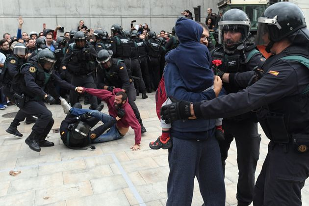 A man (back) struggles with the police as other police take hold of a man and a child holding a red flower...