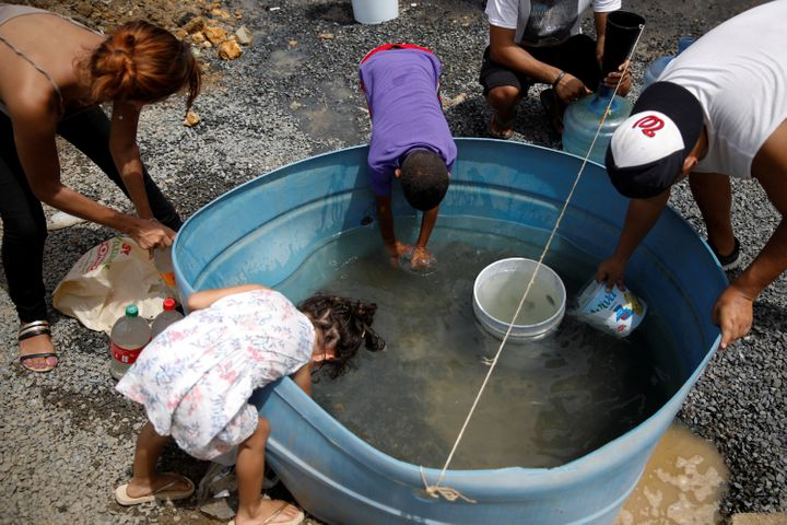 People fill containers with water in Canovanas, Puerto Rico, on Tuesday.