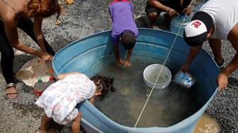 People fill containers with water at an area hit by Hurricane Maria in Canovanas, Puerto Rico, September 26, 2017. Picture taken on September 26, 2017. REUTERS/Carlos Garcia Rawlins