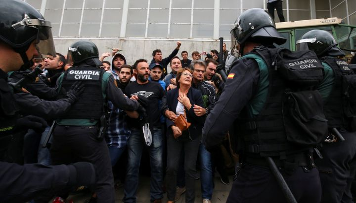 People confront Spanish Civil Guard officers outside a polling station for the banned independence referendum in Sant Julia d
