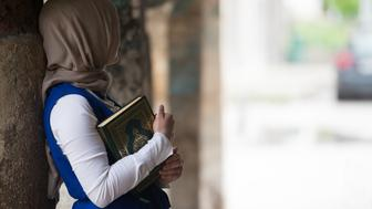 Humble Muslim Woman Is Reading The Koran Outdoors