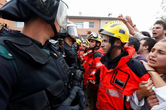 Firemen and people face off Spanish Civil Guard officers outside a polling station for the banned independence...
