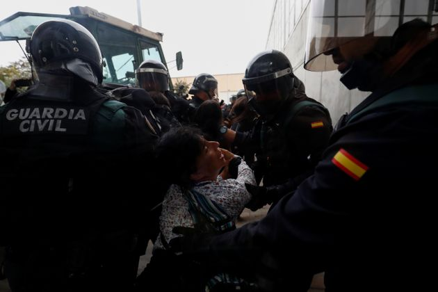 Spanish Civil Guard officers scuffle with a woman outside a polling station for the banned independence
