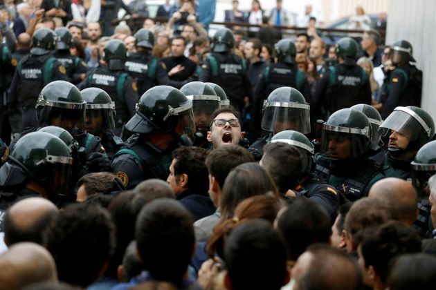 Scuffles break out as Spanish Civil Guard officers force their way through a crowd and into a polling