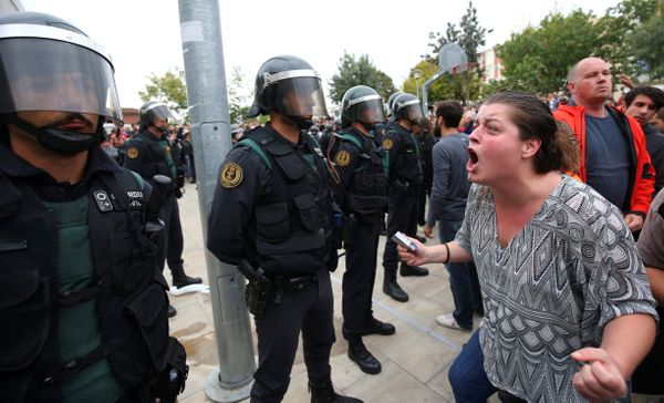 A woman screams towards Spanish Civil Guard officers outside a polling station.