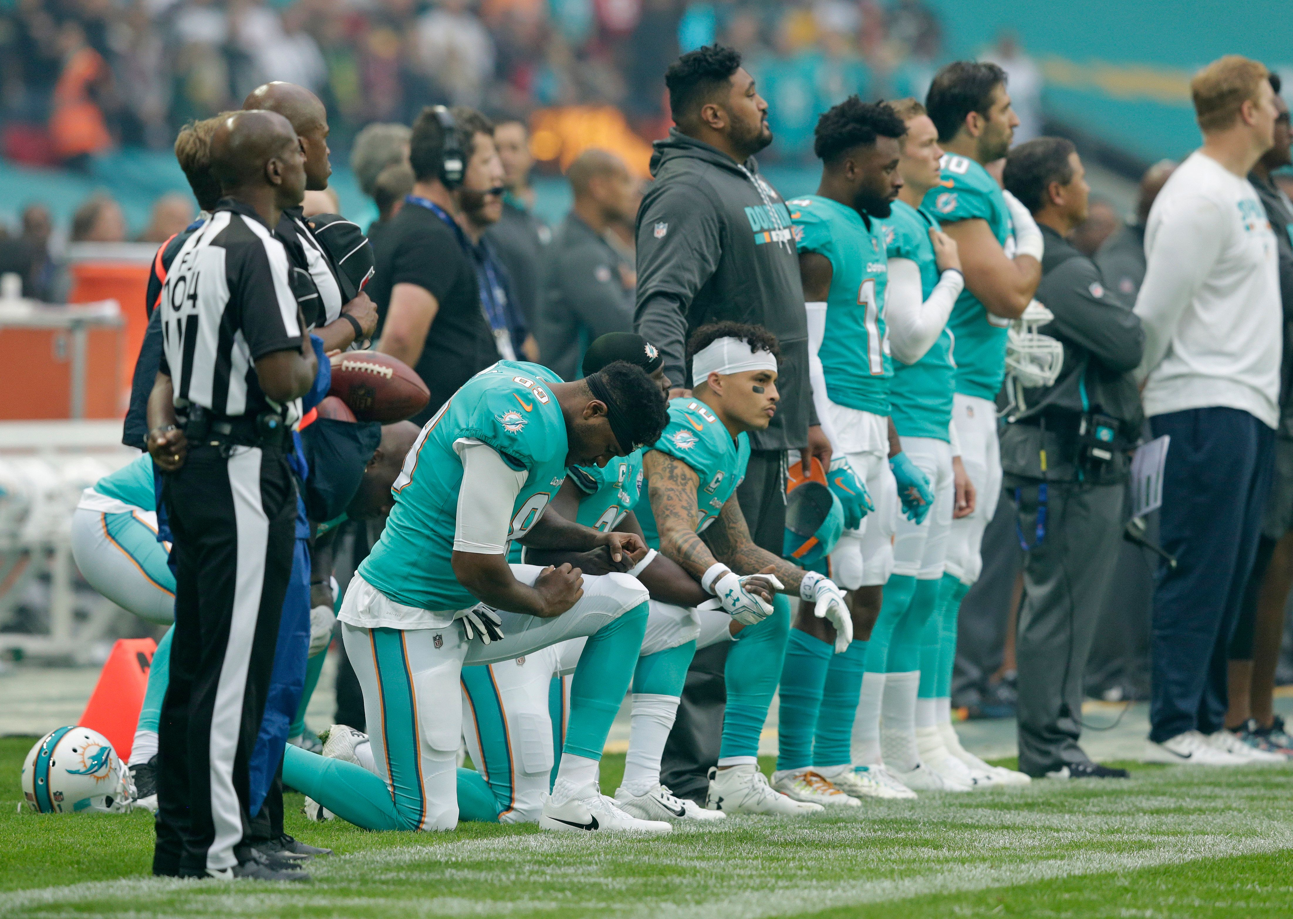 LONDON, ENGLAND - OCTOBER 01: Miami Dolphins players kneel down during the national anthem before the NFL game between the Miami Dolphins and the New Orleans Saints at Wembley Stadium on October 1, 2017 in London, England. (Photo by Henry Browne/Getty Images)