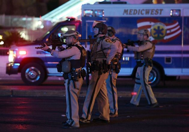 Police officers point their weapons at a car driving down closed Tropicana Ave near Las Vegas Boulevard...