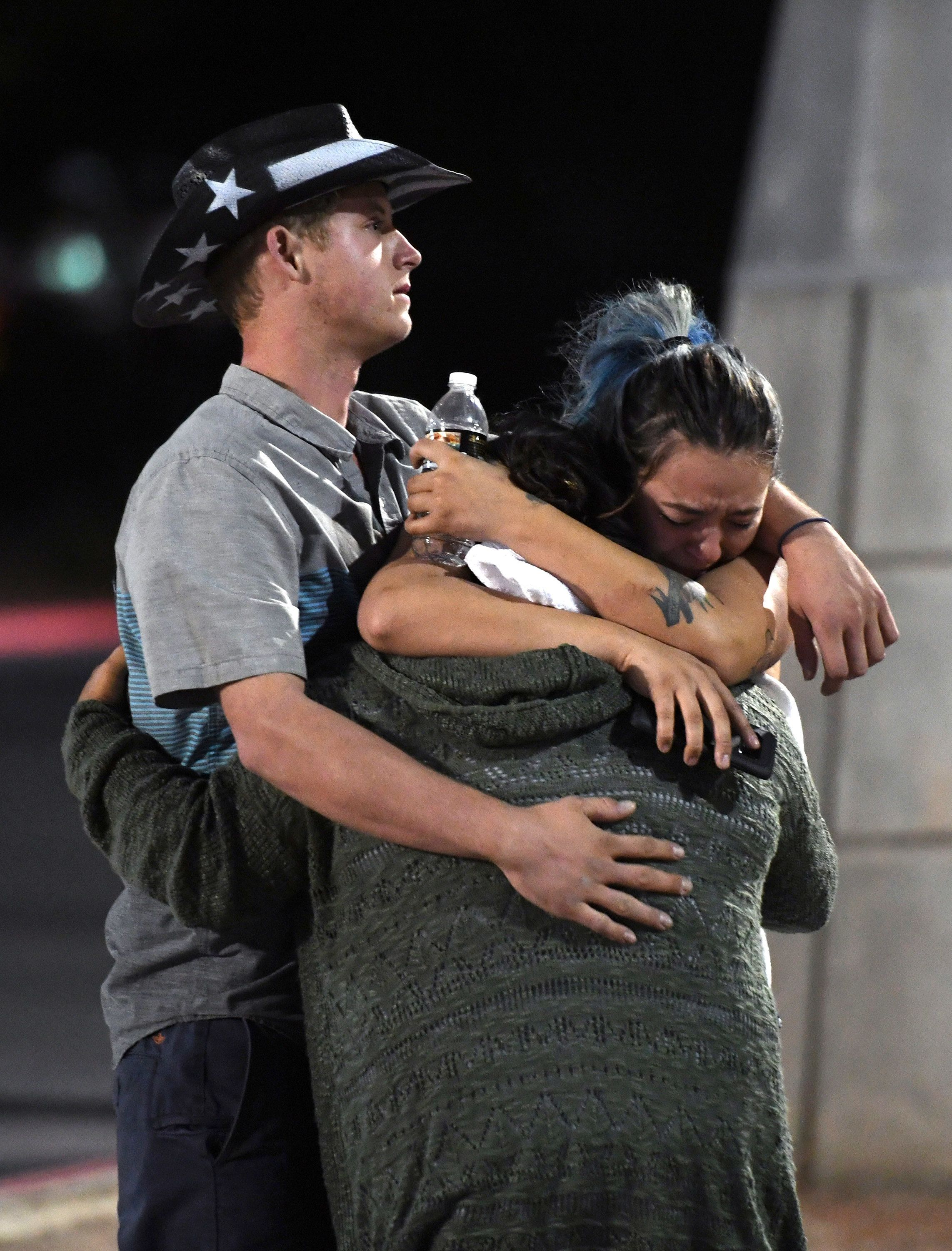 People hug and cry outside the Thomas & Mack Center after a mass shooting at the Route 91 Harvest country music festival
