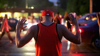 FERGUSON, MO - AUGUST 15:  Demonstrators gather along West Florissant Avenue to protest the shooting of Michael Brown on August 15, 2014 in Ferguson, Missouri. Brown was shot and killed by a Ferguson police officer on August 9. Protestors raise their hands and chant 'Hands up, don't shoot'  as a rally cry to draw attention to reports that stated Brown's hands were raised when he was shot. Tonight demonstration again ended with protestors  clashing with police followed by more looting.  (Photo by Scott Olson/Getty Images)