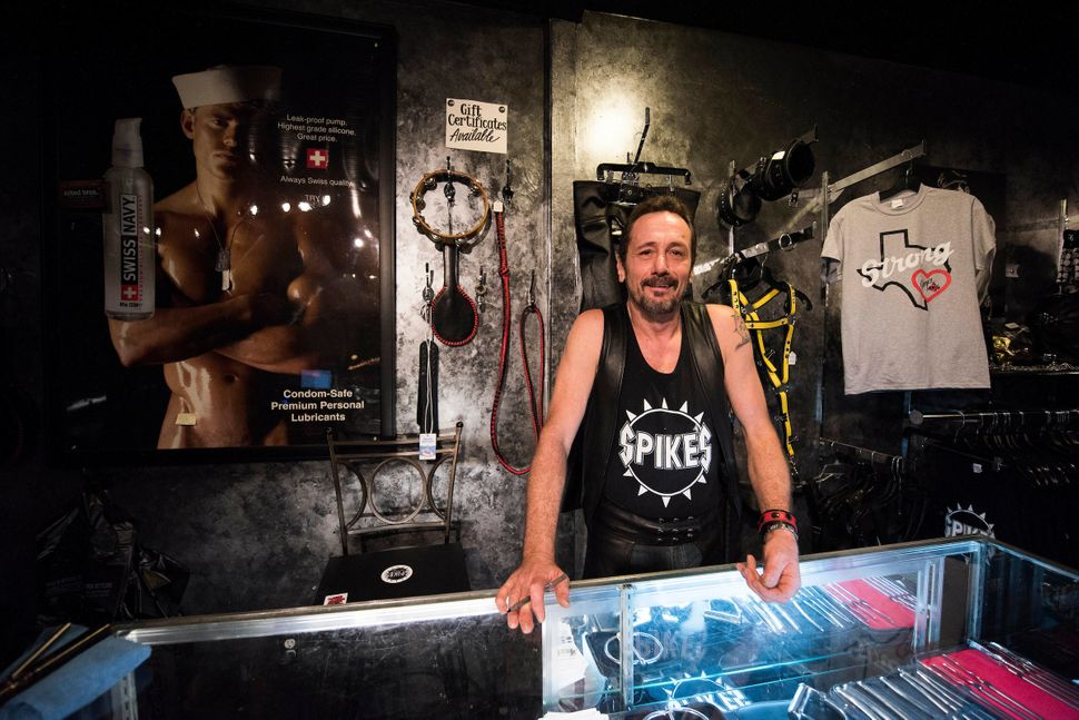 Rod Caldwell, co-owner of Spike's Leather Club in Birmingham, Alabama, stands behind a glass counterin their boutique.&