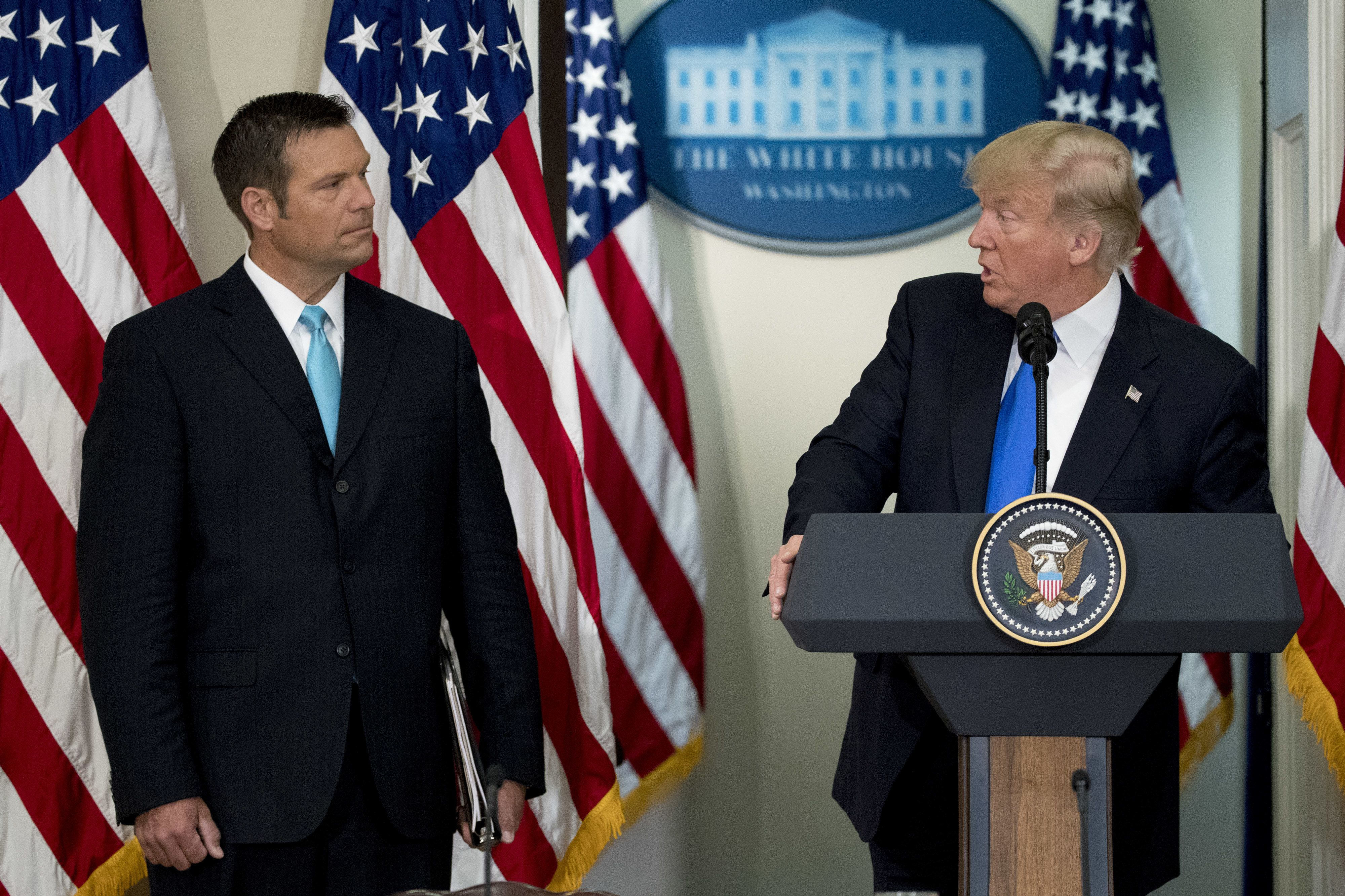 U.S. President Donald Trump speaks as Kris Kobach, Kansass secretary of state, left, listens during the initial meeting of the Presidential Advisory Commission on Election Integrity at the Eisenhower Executive Office Building in Washington, D.C., U.S., on Wednesday, July 19, 2017. Trump created the advisory commission in May, after claiming without evidence that 3 million people or more illegally voted for Hillary Clinton last year. Photographer: Andrew Harrer/Bloomberg via Getty Images