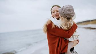 Photo of a mother and daughter playing on the beach