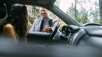 An on duty law enforcement officer, working hard at providing justice, keeping the peace, and making the country a safer place.  Here he inspects the drivers license of a person he has pulled over for speeding, given them a friendly warning about the risk and danger of their behavior and the cost of a potential ticket.