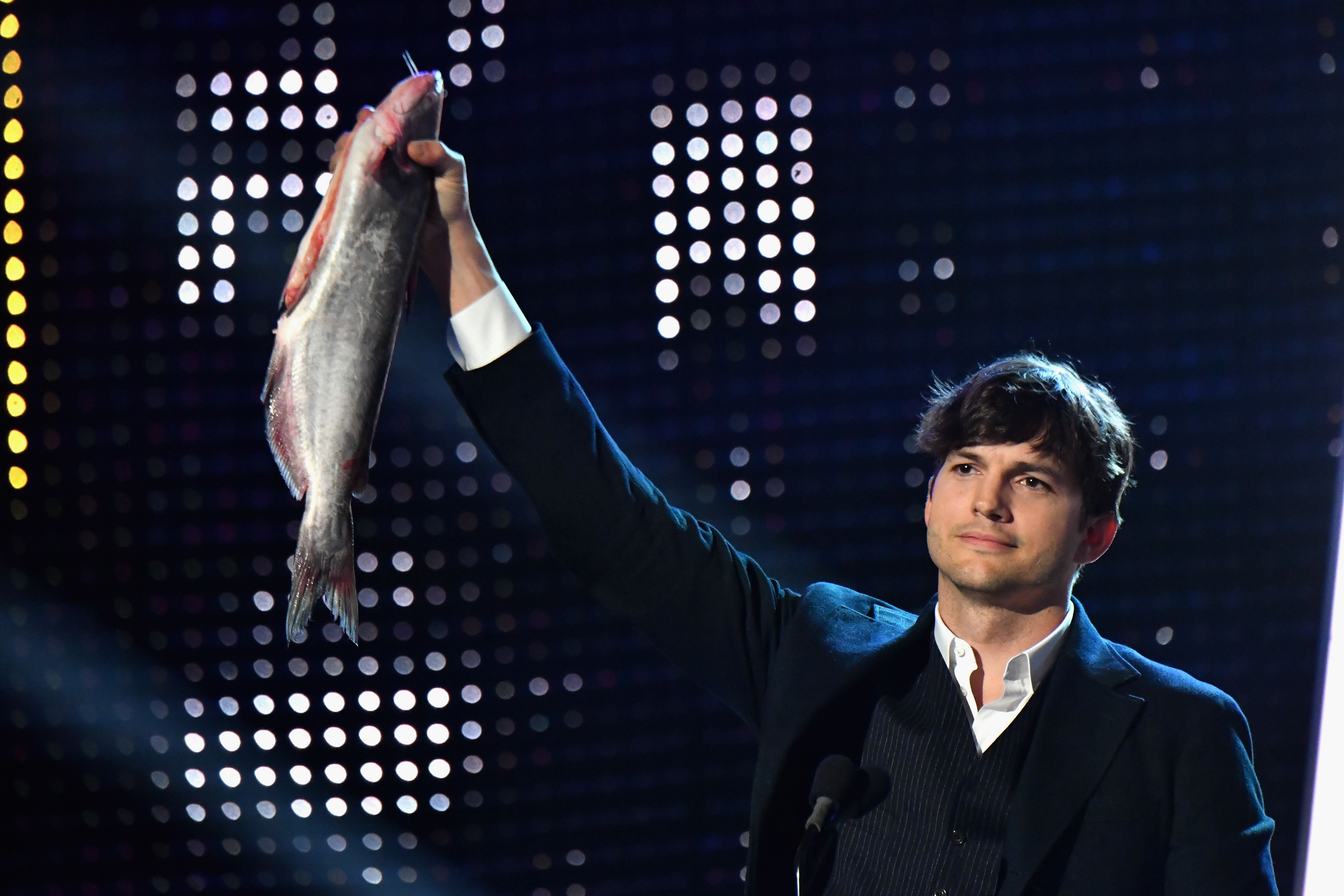 NASHVILLE, TN - JUNE 07: Ashton Kutcher raises a catfish in honor of the Nashville Predators Stanley Cup run during the 2017 CMT Music awards at the Music City Center on June 7, 2017 in Nashville, Tennessee.  (Photo by Jeff Kravitz/FilmMagic)