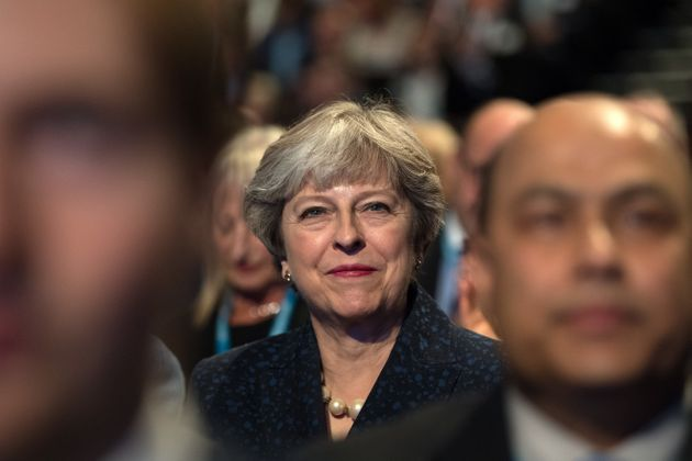 Theresa May, listens to a speech by Philip