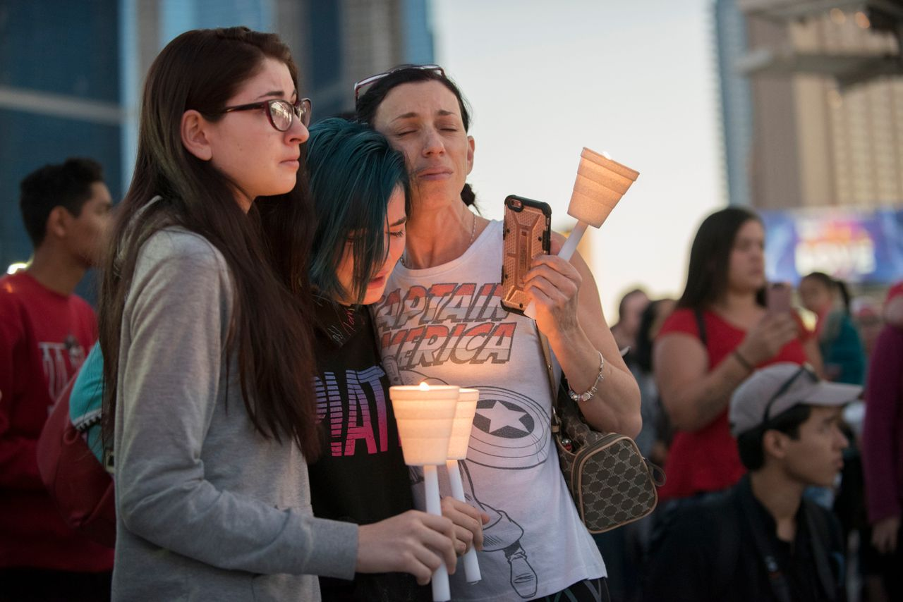 Mourners comfort each other during a candlelight vigil held on the north end of the Las Vegas strip across the street from the SLS hotel and casino on Oct. 2, 2017.