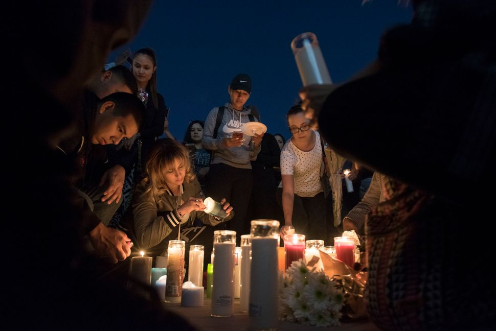 Mourners place candles and flowers on the ground during a candlelight vigil.