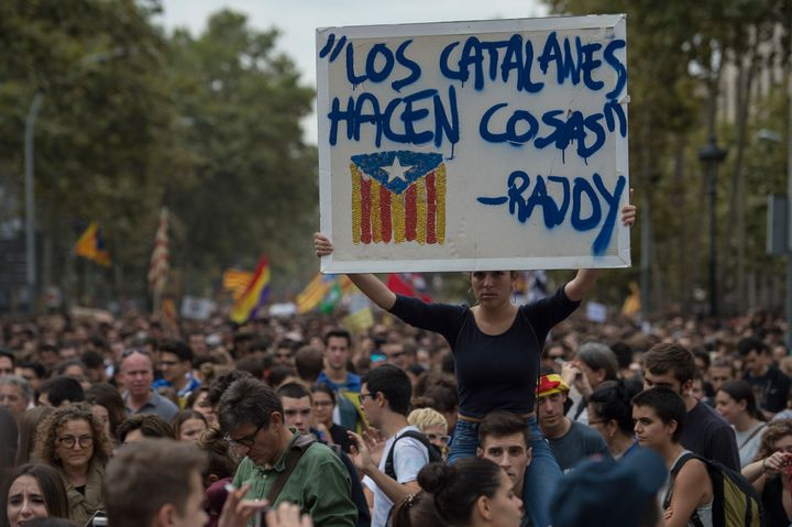 A demonstrator holds up a sign that reads a quote from the Prime Minister of Spain Mariano Rajoy: 'Catalans do things.'