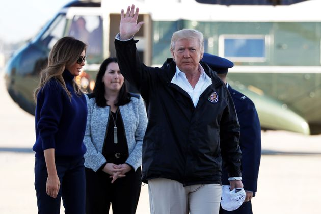 President Donald Trump waves to reporters as he and first lady Melania Trump arrive at Joint Base Andrews,...