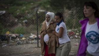 THESSALONIKI, GREECE - SEPTEMBER 25:  A pregnant refugee woman walks towards the Greek-Macedonian border near the village of Idomeni in northern Greece on September 25, 2015. Refugees who begin a journey with a hope to have high living standards away from conflicts, use Greece's Lesbos Island as a transit point on their way to Europe. After arriving in Athens from Lesbos Island, refugees get a bus or train to go to Idomeni village of Thessaloniki on the Greek Macedonian border. (Photo by Ozge Elif Kizil/Anadolu Agency/Getty Images)