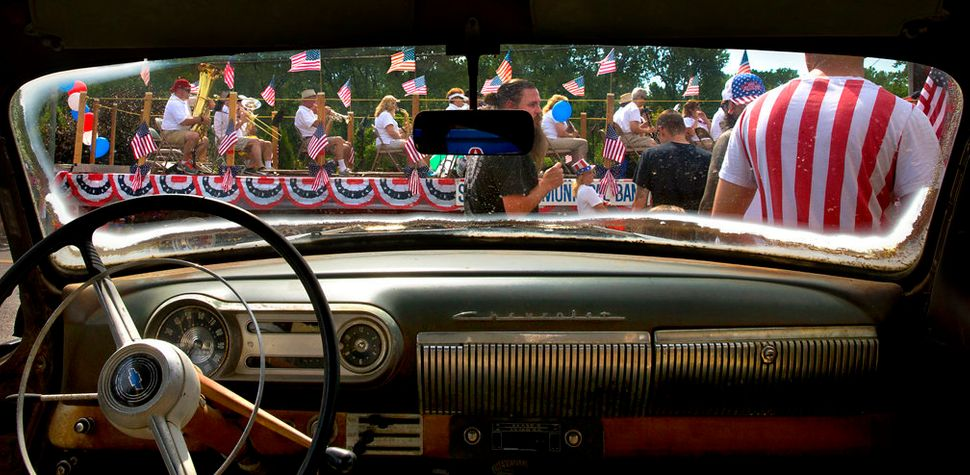 Members of the St. Charles Municipal Band roll past a 1953 Chevy on the lot of McNeil Motor Cars as the St. Charles Jaycees R