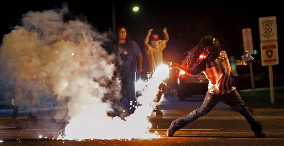Edward Crawford tosses a tear gas canister fired by police who were trying to disperse protesters in Ferguson, Missouri, on A