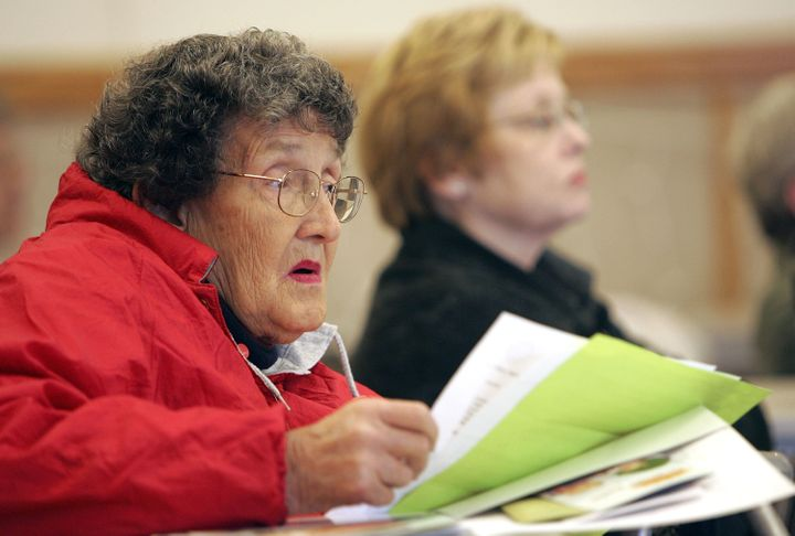 An elderly woman listens to a seminar on how to sign up during a Medicare enrollment event.