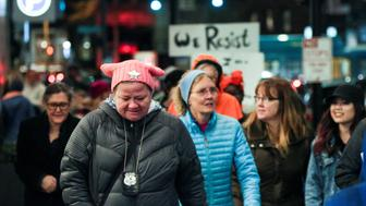 An off-duty police officer wearing a pink pussy protest hat joins other protesters as they walk through downtown Seattle during the Dress Like A Woman rally and march, held to support women's rights and to protest U.S. President Donald Trump, in Seattle, Washington, U.S. February 25, 2017. REUTERS/David Ryder