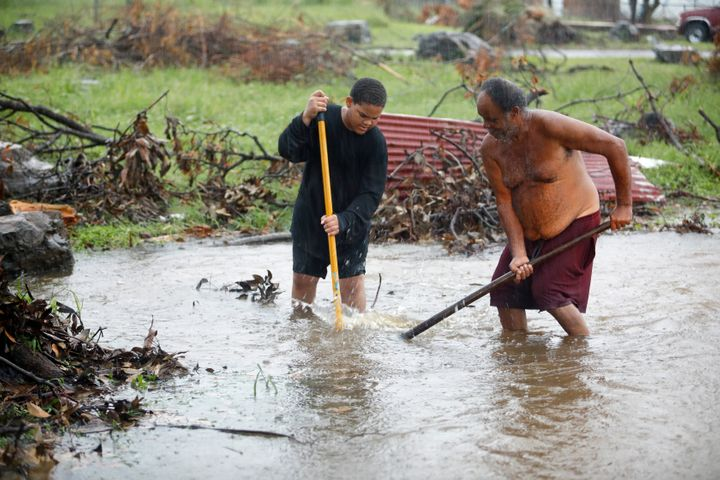 Residents of St. Croix work in floodwaters to clear a drain blocked by debris from Hurricane Maria as the island receives tor