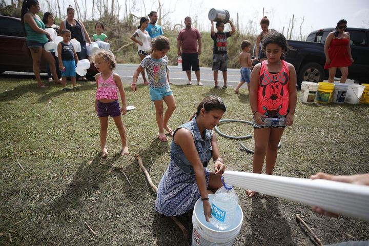 People in Corazal, Puerto Rico, fill containers with water from a natural spring on the side of the road as people deal