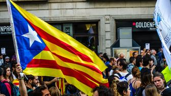 BARCELONA, CATALONIA, SPAIN - 2017/10/03: A pro-independence flag flies over the heads of protesters. Thousands of people occupying the streets of Barcelona. They are protesting against the Spanish national police's violent during the referendum. (Photo by Paco Freire/SOPA Images/LightRocket via Getty Images)