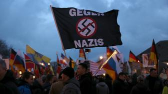 """Supporters of the anti-Islam movement """"Patriotic Europeans Against the Islamisation of the West"""" (PEGIDA) hold on a flag """"Against Nazis"""" during a demonstration in Dresden, Germany, March 21, 2016. REUTERS/Ina Fassbender"""