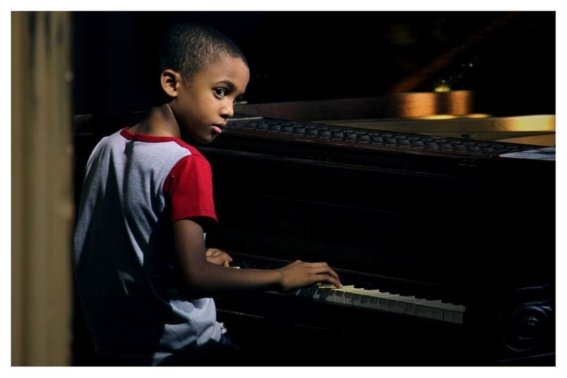 Reynaldo Guanche takes a piano lesson in a scene from <strong><em>Esteban</em></strong>