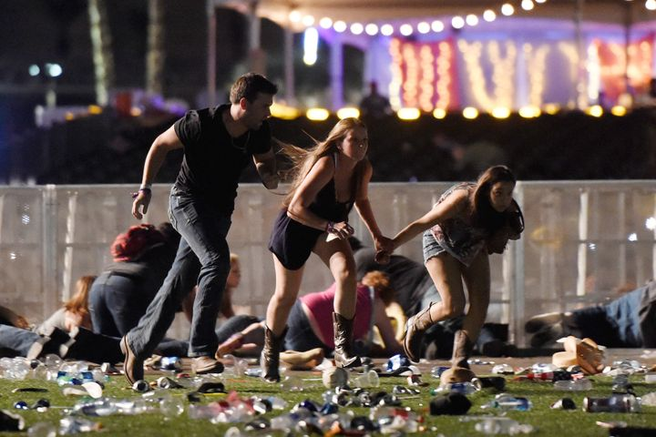 People run from the Route 91 Harvest country music festival in Las Vegas Sunday night after gunfire was heard.