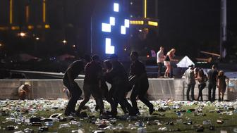 LAS VEGAS, NV - OCTOBER 01: (EDITORS NOTE: Image contains graphic content.) People carry a person at the Route 91 Harvest country music festival after apparent gun fire was heard on October 1, 2017 in Las Vegas, Nevada. There are reports of an active shooter around the Mandalay Bay Resort and Casino.  (Photo by David Becker/Getty Images)