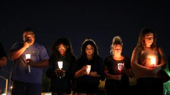 People pray during a candlelight vigil for victims of the Route 91 music festival mass shooting next to the Mandalay Bay Resort and Casino in Las Vegas, Nevada, U.S. October 3, 2017. REUTERS/Lucy Nicholson
