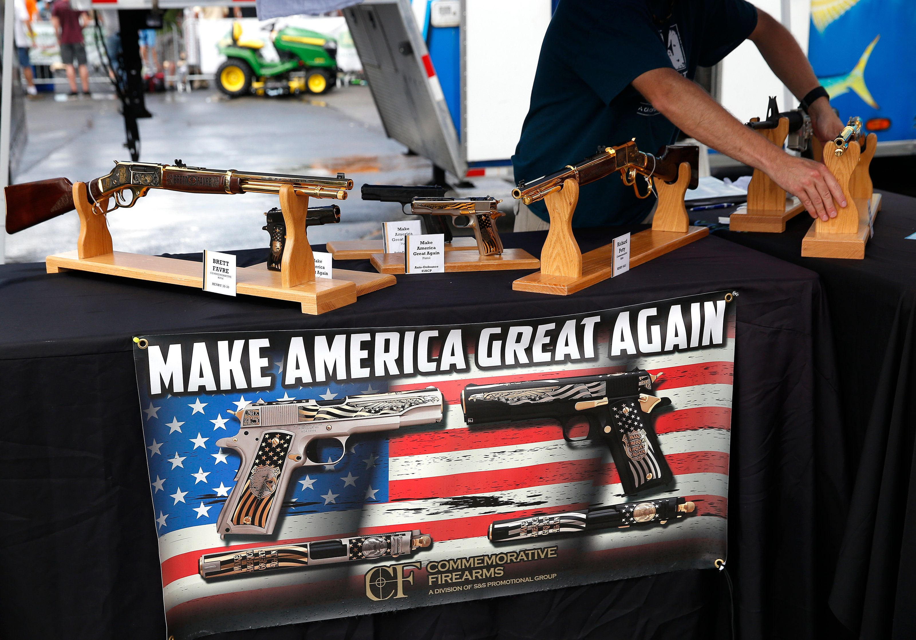 A worker rearranges the guns inside the booth at Commemorative Firearms as fans stopped by to check out...