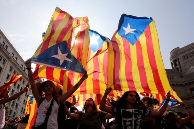 People hold on to Catalan separatist flags on top of an air vent during a demonstration two days after...