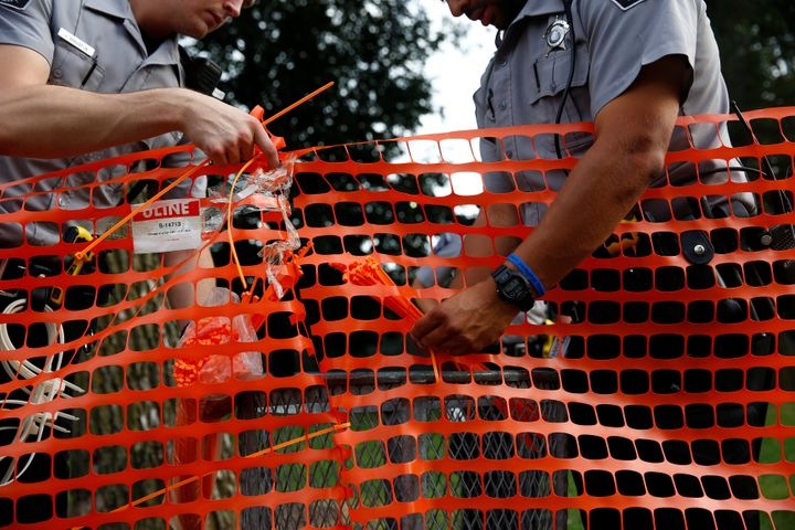 Members of the Milwaukee County Sheriff's department erect a fence around Sherman Park after disturbances following the polic